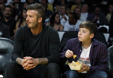 Soccer star David Beckham (L) and his son Brooklyn watch the Los Angeles Lakers play the Denver Nuggets during Game 1 of their first round NBA Western Conference basketball playoff game in Los Angeles, California, April 29, 2012. REUTERS/Lucy Nicholson