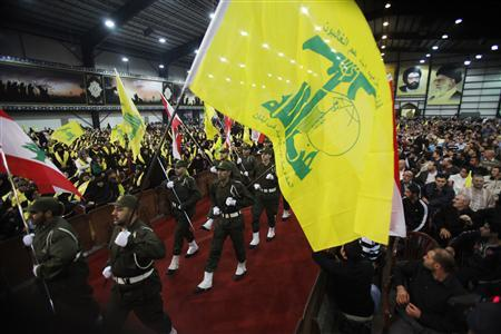 Lebanon's Hezbollah members carry Hezbollah and Lebanese flags as they parade during a rally marking the party's Martyrs Day in Beirut's suburbs November 12, 2012. REUTERS/Sharif Karim