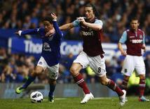 O jogador do West Ham United Andy Carroll (D) disputa lance com Steven Pienaar, do Everton, em jogo do Campeonato Inglês em 12 de maio. Nesta terça-feira, o atacante foi cortado de amistosos da Inglaterra contra Irlanda e Brasil. REUTERS/Darren Staples