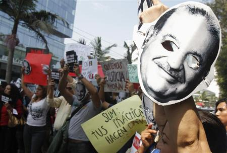 People protest holding masks printed with the face of Mexican telecommunications and retail tycoon Carlos Slim as he attends the Meeting of Latin American Businessmen at a hotel in Lima May 3, 2013. REUTERS/Enrique Castro-Mendivil