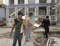 سكان يتفقدون موقع انفجار قرب مسجد في الحلة جنوبي بغداد يوم الثلاثاء - رويترز