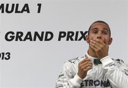 Mercedes Formula One driver Lewis Hamilton of Britain reacts on the winners' podium during the victory ceremony after the Chinese F1 Grand Prix at the Shanghai International Circuit, April 14, 2013. REUTERS/Kim Kyung-Hoon/Files