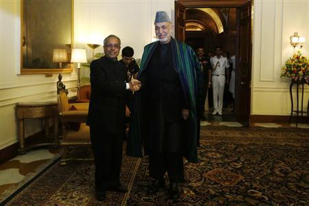 Afghanistan's President Hamid Karzai (R) shakes hands with his Indian counterpart Pranab Mukherjee ahead of their meeting at the Rashtrapati Bhavan presidential palace in New Delhi May 21, 2013. REUTERS/Adnan Abidi