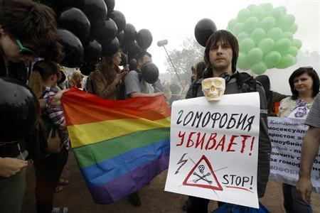 A gay rights activist holds a placard during a rally to mark the international day against homophobia in St. Petersburg May 17, 2013. The placard reads ''Homophobia kills!'' REUTERS/Alexander Demianchuk