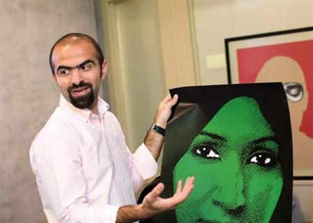 Kuwaiti graphic designer Mohammad Sharaf talks about his work in his office in Hawalli, May 1, 2013. After two lacklustre decades, Kuwait is experiencing a quiet revival of an arts scene once known as the most avant-garde in the Gulf, thanks to a new generation eager to tackle sensitive issues using cutting-edge art forms. REUTERS/Stephanie McGehee