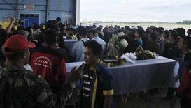 Горняки с шахты компании Freeport стоят у гробов с телами своих коллег, погибших в результате обрушения туннеля, в индонезийском городе Тимика 22 мая 2013 года. Горнорудная компания Freeport McMoRan Copper and Gold Inc заявила, что не будет возобновлять производство на втором по величине в мире медном руднике в Индонезии после обрушения туннеля и гибели 28 рабочих, пока не будет убеждена в безопасности шахты. REUTERS/Muhammad Yamin