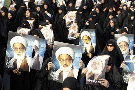 Anti-government protesters hold posters of Shi'ite cleric Ayatollah Sheikh Isa Qassim during an anti-government protest organised by Bahrain's main opposition group Al Wefaq, in Budaiya, west of Manama May 17, 2013. REUTERS/Hamad I Mohammed