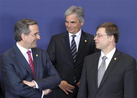 (L-R) Greece's Prime Minister Antonis Samaras listens to Austria's Chancellor Werner Faymann and Latvia's Prime Minister Valdis Dombrovskis as they pose for a family photo during a European Union leaders summit in Brussels May 22, 2013. REUTERS/Laurent Dubrule