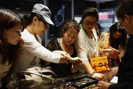 Customers try 24K gold bracelets inside a jewellery store at Hong Kong's Mongkok district April 23, 2013. REUTERS/Bobby Yip/Files