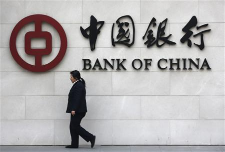 A woman walks past a sign of Bank of China at its branch in Beijing in this March 26, 2013 file photo. REUTERS/Kim Kyung-Hoon/Files