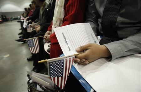 Candidates hold U.S. flags during a naturalization ceremony to become new U.S. Citizens at Convention Center in Los Angeles, California February 27, 2013. REUTERS/Mario Anzuoni