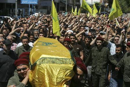 Supporters of Hezbollah and relatives of Hezbollah member Hussein Ahmad Abu Hasan carry his coffin during his funeral in Beirut's suburbs May 21, 2013. REUTERS/Issam Kobeisy