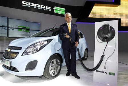 Sergio Rocha, president and CEO of GM Korea poses next to Spark EV at the Seoul motor show in Goyang, north of Seoul March 28, 2013. REUTERS/Lee Jae-Won