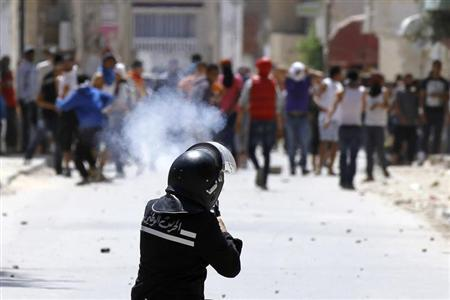 A riot police officer fires teargas during clashes with supporters of Islamist group Ansar al-Sharia at Hai al Tadamon in Tunis May 19, 2013. REUTERS/Anis Mili