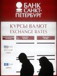 Люди проходят мимо вывески пункта обмена валюты в Санкт-Петербурге 25 марта 2013 года. Рубль торгуется с минимальными изменениями в четверг утром, поддержку могут оказывать продажи экспортной валютной выручки под крупные налоги следующей недели, тогда как в целом внешний фон сейчас играет против рубля и далее может оказать негативное влияние на российскую валюту. REUTERS/Alexander Demianchuk