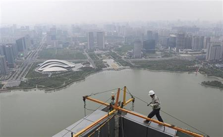 A worker walks on the roof of an office building construction site near a lake in Hefei, Anhui province May 6, 2013. REUTERS/Stringer