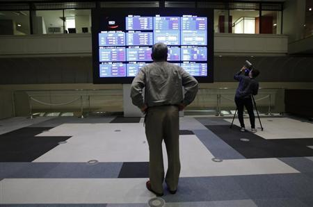 A visitor looks at the stock quotation board at the Tokyo Stock Exchange in Tokyo May 20, 2013. REUTERS/Toru Hanai