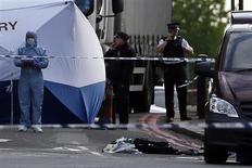 Полиция на месте убийства в Вулидже, юго-восточный Лондон 22 мая 2013 года. Британский солдат был сбит машиной и затем жестоко убит холодным оружием в среду на улице в пригороде Лондона людьми, выкрикивавшими исламистские лозунги, и власти расценили случившееся как теракт. REUTERS/Stefan Wermuth