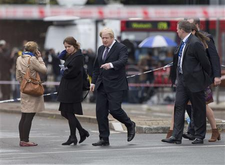 London Mayor Boris Johnson (C) points near the scene of the killing of a British soldier in Woolwich, southeast London May 23, 2013. REUTERS-Neil Hall