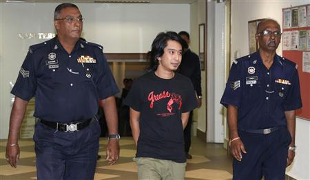 Activist Adam Adli is escorted by police at a courthouse in Kuala Lumpur May 23, 2013. REUTERS/Stringer