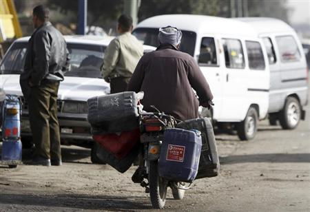 A motorcyclist carries fuel containers after filling them up from a petrol station as he passes other motorists in queue in Toukh, El-Kalubia governorate, about 25 km (16 miles) northeast of Cairo March 12, 2013. REUTERS/Amr Abdallah Dalsh