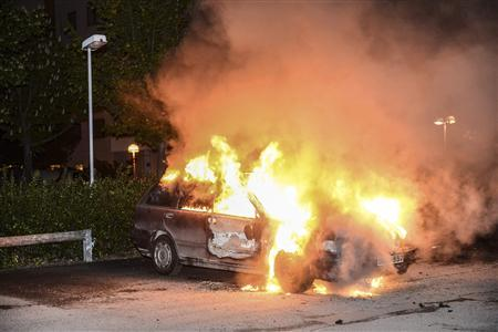 A car set on fire burns, following riots in the Stockholm suburb of Kista late May 21, 2013, in this picture provided by Scanpix. Sweden's capital has been hit by some of its worst riots in years after youths scorched dozens of cars, attacked a police station and threw stones at rescue services in its poor immigrant suburbs for a third night running. REUTERS/Fredrik Sandberg/Scanpix