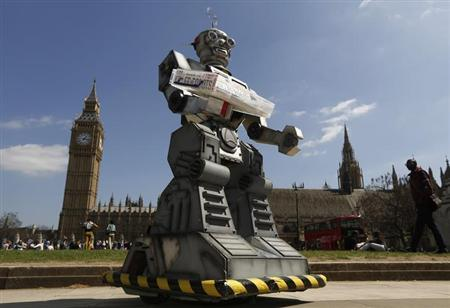 A robot is pictured in front of the Houses of Parliament and Westminster Abbey as part of the Campaign to Stop Killer Robots in London April 23, 2013. REUTERS/Luke MacGregor