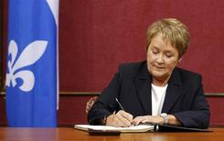 Quebec's Premier-elect Pauline Marois signs documents during the swearing-in ceremony for the Parti Quebecois members of the National Assembly (MNA) at the Quebec Legislature in Quebec City, September 17, 2012. REUTERS/Mathieu Belanger