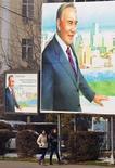 Женщины проходят мимо щитов с изображением президента Казахстана Нурсултана Назарбаева, подготовленных по случаю празднования Дня первого президента, в Алма-Ате 28 ноября 2012 года. Верхняя палата парламента Казахстана в четверг одобрила предложенную президентом национализацию пенсионной системы и поддержала повышение на пять лет пенсионного возраста для женщин, несмотря на ропот среди 16,6-миллионного населения богатой нефтью и металлами страны. REUTERS/Shamil Zhumatov