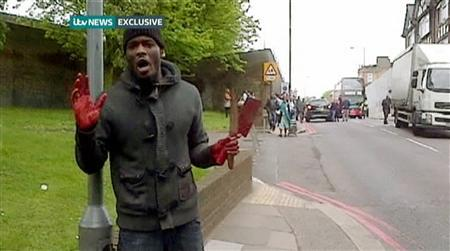 A man with bloodied hands and knives speaks to a camera, in a still image from amateur video that shows the immediate aftermath of an attack in which a man was killed in southeast London May 22, 2013. REUTERS-ITV News via Reuters TV