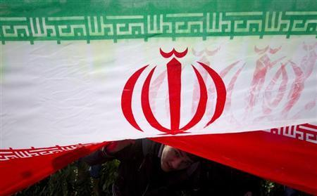 A demonstrator peeks from under an Iranian flag during a ceremony to mark the 33rd anniversary of the Islamic Revolution, in Tehran's Azadi square, February 11, 2012. REUTERS/Caren Firouz