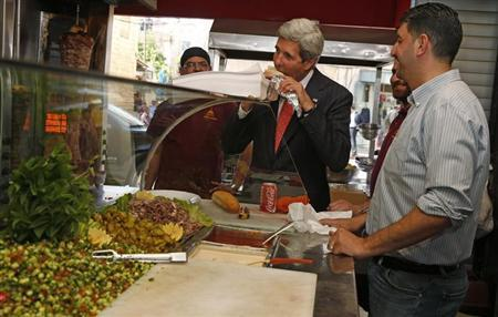 U.S. Secretary of State John Kerry (2nd R) samples some food as he visits a restaurant in the West Bank city of Ramallah, May 23, 2013. REUTERS/Jim Young
