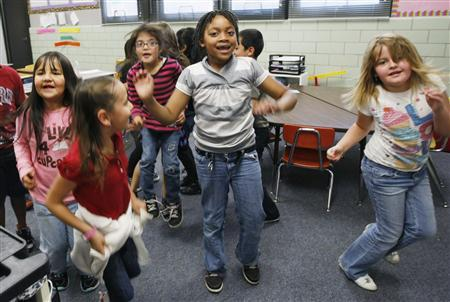 Students at Rose Hill Elementary School jump around doing a counting exercise that is also aerobic exercise in their classroom in Commerce City, Colorado May 1, 2012. REUTERS/Rick Wilking