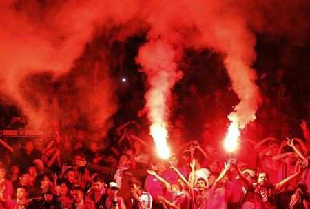Indonesian supporters lights flares during a 2015 Asian Cup qualifying soccer match in Jakarta March 23, 2013. REUTERS/Beawiharta