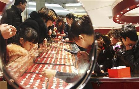 Customers are reflected in a mirror as they look at gold accessories at a gold store in Xuchang, Henan province, in this February 15, 2013 file photo. REUTERS/China Daily/Files