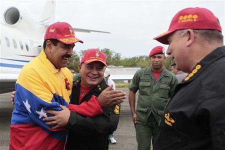 Venezuela's President Nicolas Maduro (L) embraces National Assembly President Diosdado Cabello while speaking to Defense Minister Diego Molero (R) in the island of La Orchila May 22, 2013.REUTERS/Miraflores Palace/Handout