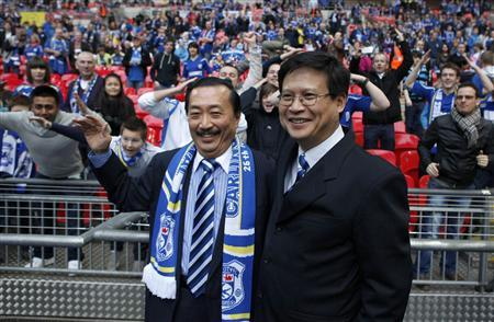 Cardiff City's Malaysian Chairman Chan Tien Ghee (R) and Malaysian owner Vincent Tan smile ahead of their English League Cup final soccer match against Liverpool at Wembley Stadium in London in this February 26, 2012 file photo. REUTERS/Andrew Winning/File