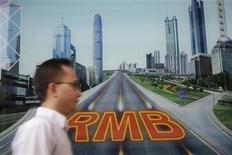 图为在香港一家银行,一名男子经过人民币标识。REUTERS/Tyrone Siu