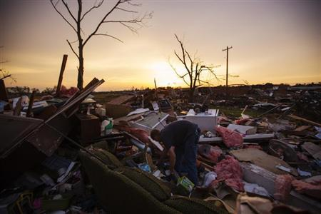 Jason Owen digs through debris as he helps his mother to salvage items from her uncle's home after it was almost destroyed by a tornado in Moore, Oklahoma, May 23, 2013. REUTERS/Lucas Jackson