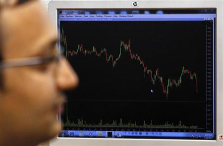 A broker works while sitting in front of a screen displaying live stock quotes on the floor of a trading firm in Mumbai May 23, 2013. REUTERS/Vivek Prakash