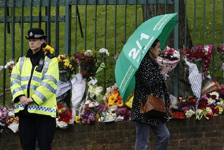 A policewoman stands near floral tributes for Drummer Lee Rigby, of the British Army's 2nd Battalion The Royal Regiment of Fusiliers, which are lined at a security fence outside an army barracks near the scene of his killing in Woolwich, southeast London May 24, 2013. REUTERS-Luke MacGregor