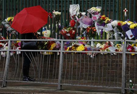 A woman reads messages left with floral tributes for Drummer Lee Rigby, of the British Army's 2nd Battalion The Royal Regiment of Fusiliers, which are lined at a security fence outside army barracks near the scene of his killing in Woolwich, southeast London May 24, 2013. REUTERS-Luke MacGregor