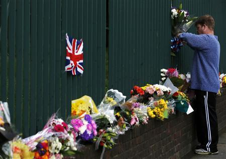 A man leaves a floral tribute for Drummer Lee Rigby, of the British Army's 2nd Battalion The Royal Regiment of Fusiliers, at a security fence outside army barracks near the scene of his killing in Woolwich, southeast London May 24, 2013. REUTERS-Luke MacGregor