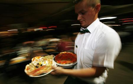 A waiter carries pizza at a restaurant in Rome, May 11, 2007. REUTERS/Dario Pignatelli