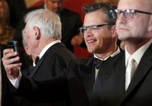 "Cast member Matt Damon (C) takes pictures with his mobile phone after the screening of the film ""Behind the Candelabra"" by Steven Soderbergh (R) in competition during the 66th Cannes Film Festival in Cannes May 21, 2013. REUTERS/Regis Duvignau"