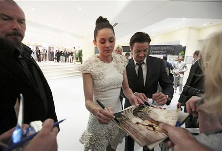 Cast members Marion Cotillard (C) and Jeremy Renner (R) sign autographs after a news conference for the film ''The Immigrant'' during the 66th Cannes Film Festival in Cannes May 24, 2013. REUTERS/Eric Gaillard