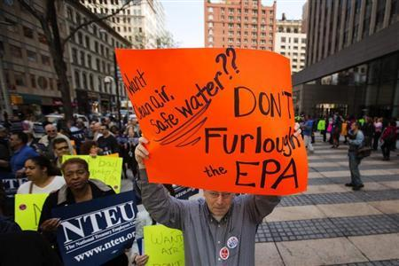 A federal employee holds up a sign protesting the effects of sequestration and the practice of furloughs at a gathering in New York, May 7, 2013. REUTERS/Lucas Jackson