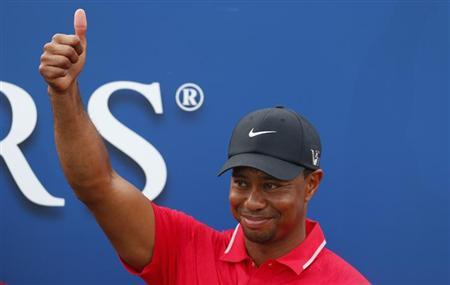 Tiger Woods reacts after being presented with The Players Championship trophy after winning the PGA golf tournament at TPC Sawgrass in Ponte Vedra Beach, Florida May 12, 2013. REUTERS/Chris Keane