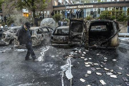A bystander checks the debris around a row of burnt cars in the suburb of Rinkeby after youths rioted in several different suburbs around Stockholm May 23, 2013. REUTERS/Fredrik Sandberg/Scanpix