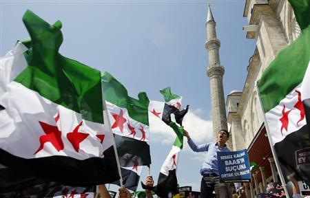 Demonstrators shout Islamic slogans as they wave Syrian opposition flags during a protest against Syria's President Bashar al-Assad at the courtyard of Fatih mosque in Istanbul May 24, 2013. The sign reads, ''Being silent means to be take part in the crime of Baath''. REUTERS/Murad Sezer